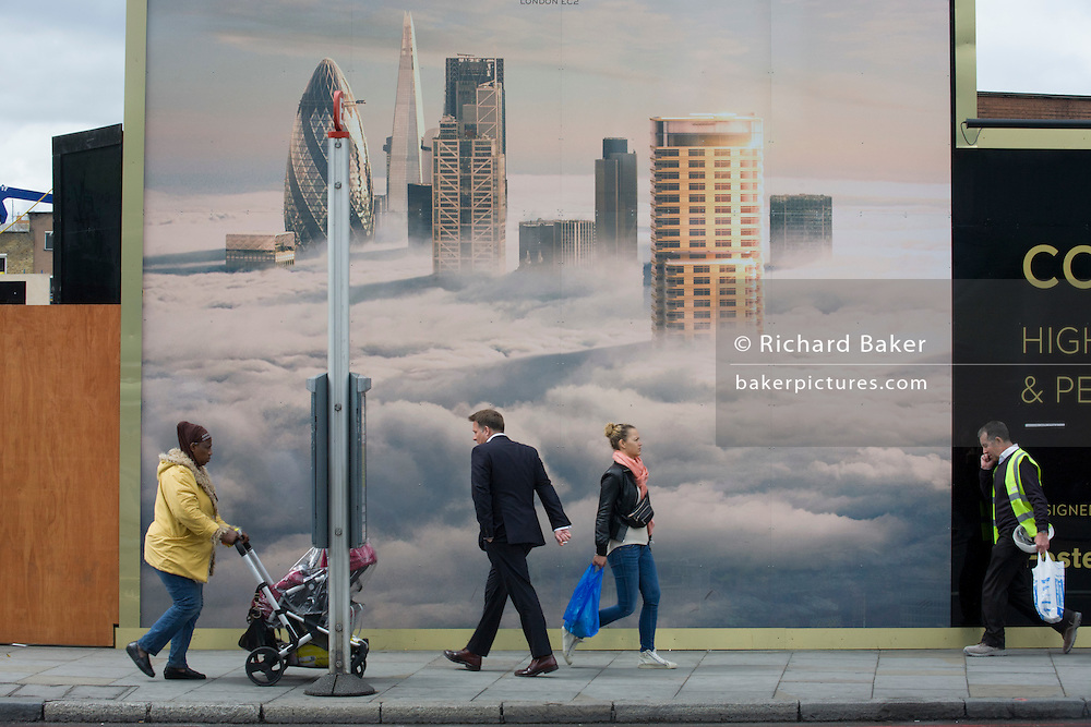 People walk beneath a property developer's billboard showing a large aerial image of London skyscrapers in low cloud.