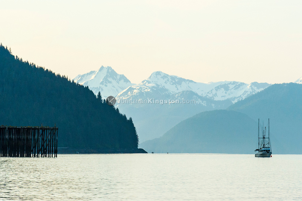 A fishing boat passes a pier with snow capped mountains in the background.