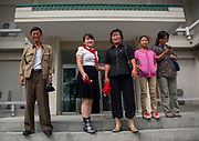 Fashion in North Korea<br /> <br /> In every corner of the earth, women love to look beautiful and keep up with the latest fashion trends. The women of North Korea are no different. Fashion is taken seriously here. But in North Korea, women do not read Elle or Vogue; they just glimpse a few styles by watching TV or by observing the few foreigners who come to visit. In the hermit kingdom, clothing also reflects social status. If you have foreign clothes it means you travel and are consequently close to the centralized power. Chinese products have inundated the country, adding some color to the traditional outfits that were made of vynalon fiber. But citizens beware, too much style means you're forgetting the North Korean juche, the ethos of self-reliance that the country is founded on! But the youth tend to neglect it despite the potential consequences.<br /> <br /> Photo shows: An upper class family leaving an expensive restaurant in Pyongyang. The bright colors from the Chinese clothes are easy to spot on the teenager while her sister proudly wears her Pioneer uniform. The mother has kept her boots.<br /> ©Eric Lafforgue/Exclusivepix Media