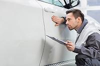 Young male repair worker examining car in automobile repair shop