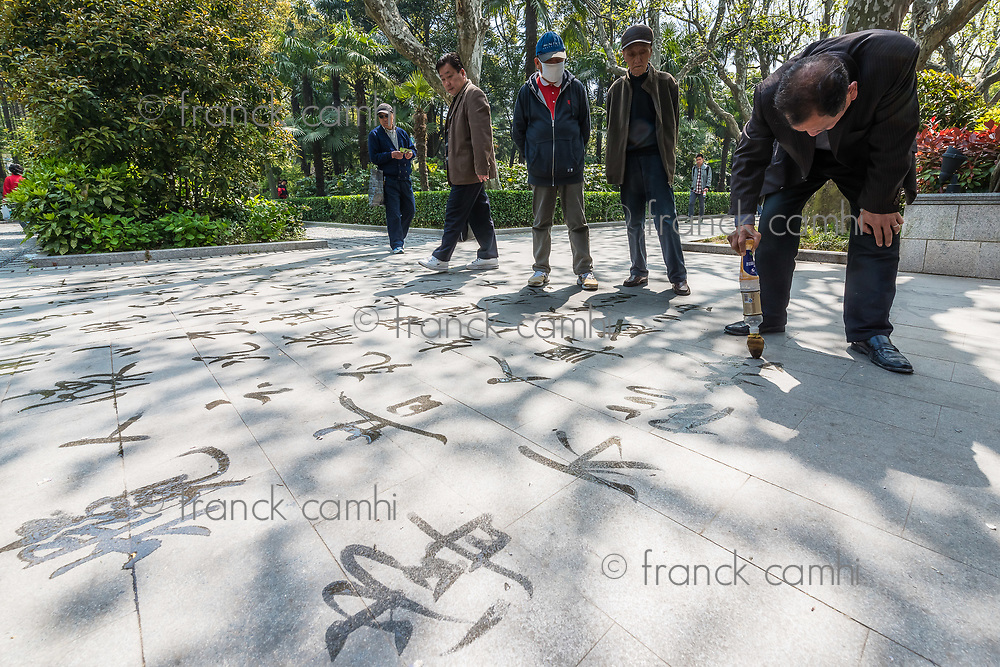 Shanghai, China - April 7, 2013: man writing chinese calligraphy with water in fuxing park at the city of Shanghai in China on april 7th, 2013