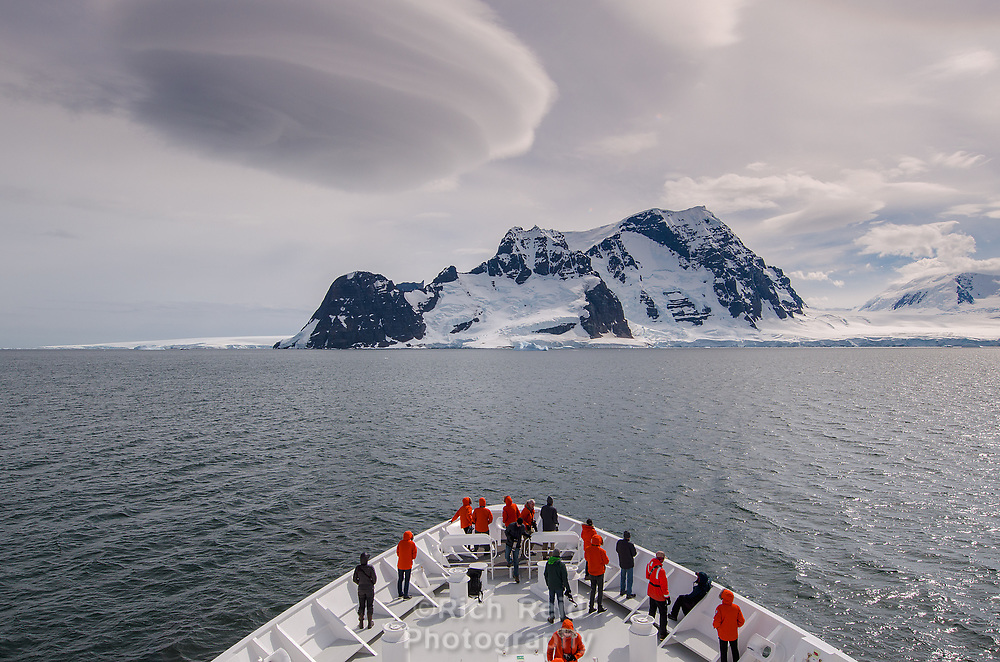 Lenticular cloud forming over Adelaide Island and bow of a ship in Antarctica.