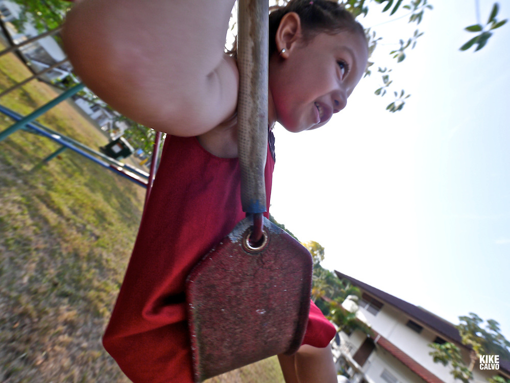 Model released photograph of a latin girl playing outdoors on a swing