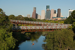 Kayaker paddling under pedestrian bridge  along Buffalo Bayou with Houston, Texas skyline in the background.