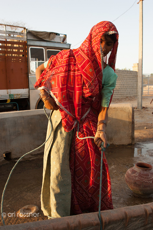 Traditional woman pumping water at the well