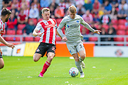 Andy Cannon (#14) of Portsmouth FC runs past Grant Leadbitter (#23) of Sunderland AFC during the EFL Sky Bet League 1 match between Sunderland and Portsmouth at the Stadium Of Light, Sunderland, England on 17 August 2019.