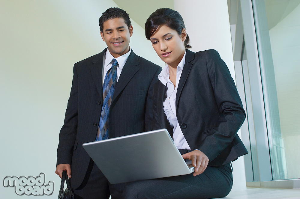 Business man and woman using laptop in hallway, low angle view