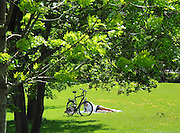Berlin, GERMANY.   Cyclist, relaxes reading the paper and enjoying the sun in the ground surrounding the Reichstag, Sunday  01/05/2011 [Mandatory Credit; Peter Spurrier/Intersport-images] Street Photos