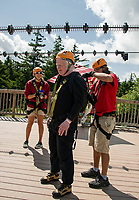Andrew Lebs gets his zipline apparatus repacked as he heads towards the second stage of Gunstock Mountain's Zipline Thursday afternoon.  (Karen Bobotas/for the Laconia Daily Sun)