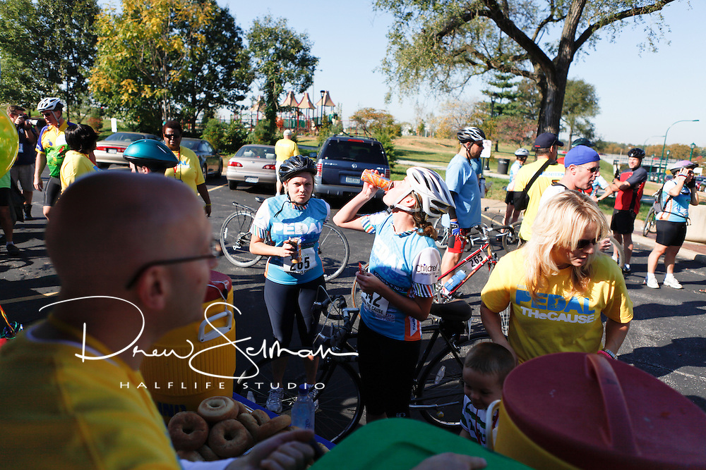9-OCT-2010 -- ST LOUIS - Riders rest at the second rest stop outside the School for the Deaf in the Central West End in St Louis on their way to the finish line in front of Soldier's Memorial in downtown St. Louis in Saturday's inaugural Pedal the Cause bicycle ride.  Over 700 people participated and the ride raised in excess a reported $1million for cancer research in St. Louis.  Pedal the Cause was founded as an annual cycling event that seeks to provide and direct net funding for cancer research, cancer discovery grants and clinical translational care on best ideas not currently eligible for federal funds.  With 100% of donations remaining in St. Louis, the event was started by Bill Koman, a St Louis business man and himself a cancer survivor.