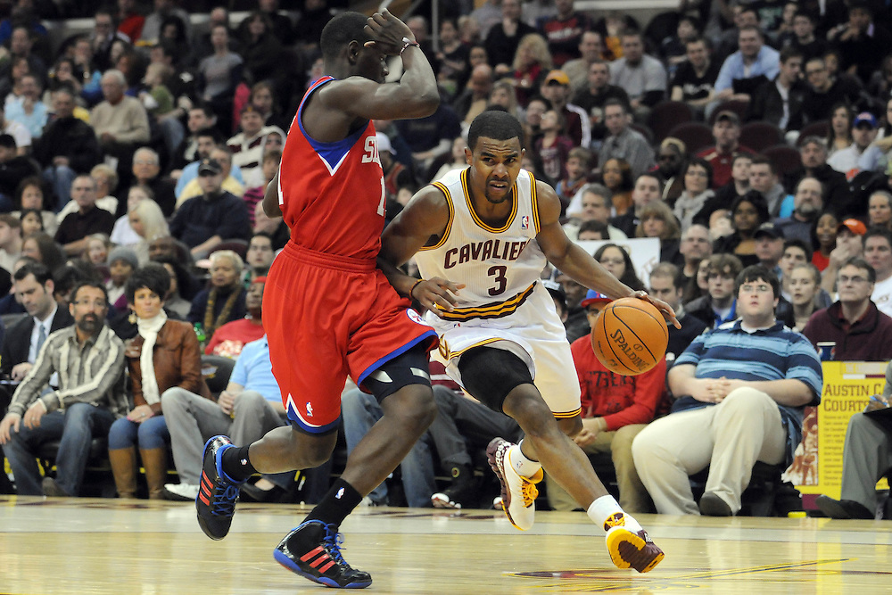 Feb. 27, 2011; Cleveland, OH, USA; Philadelphia 76ers point guard Jrue Holiday (11) tries to stop Cleveland Cavaliers point guard Ramon Sessions (3) during the third quarter at Quicken Loans Arena. The 76ers beat the Cavaliers 95-91.Mandatory Credit: Jason Miller-US PRESSWIRE
