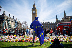 © Licensed to London News Pictures. 25/03/2017. London, UK. A woman wearing an European Union flag pays her respects to the victims of Westminster terror attack in Parliament Square, London on 25 March 2017. Photo credit: Tolga Akmen/LNP