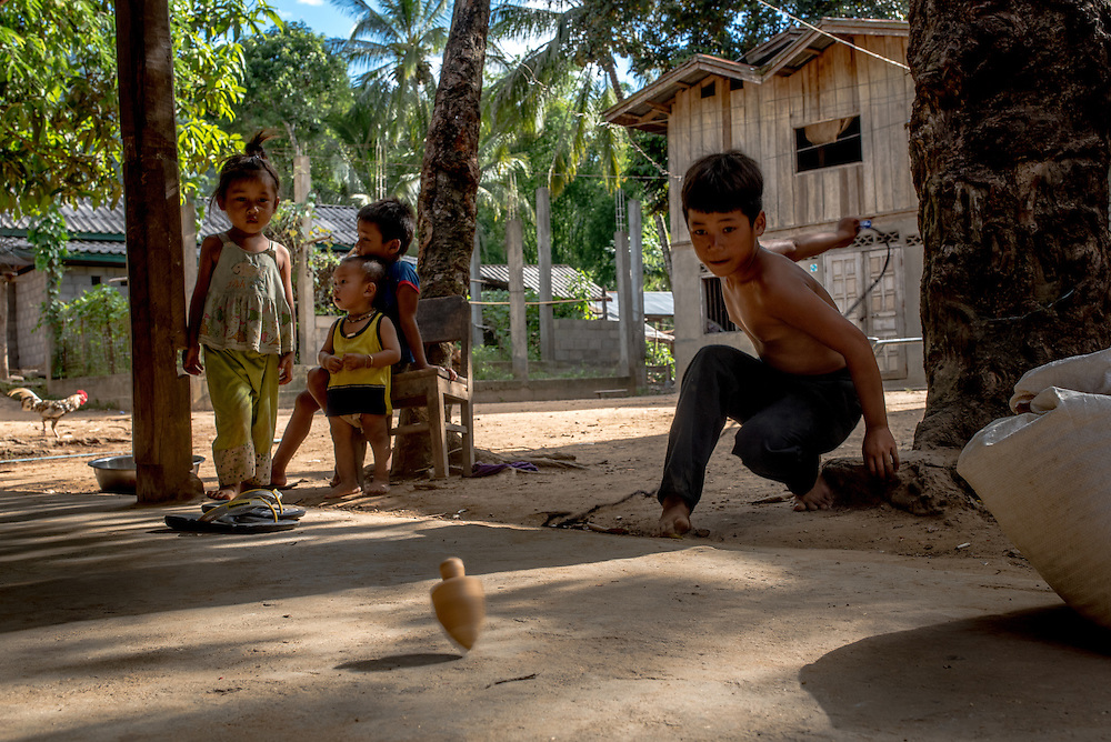 Children play with spinning tops in the village of Khoc Kham.