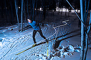 Cross-country skier at night in the woods with a light trail.