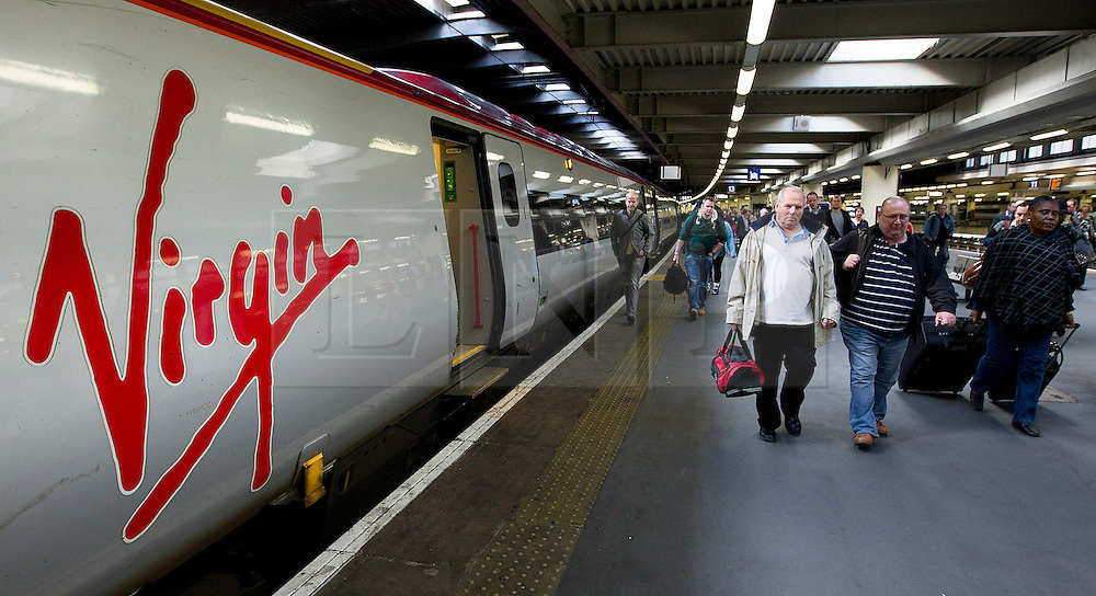 © Licensed to London News Pictures. 04/10/2012. LONDON, UK. Passengers walk past a Virgin train at Euston Station in London.  Photo credit: Matt Cetti-Roberts/LNP