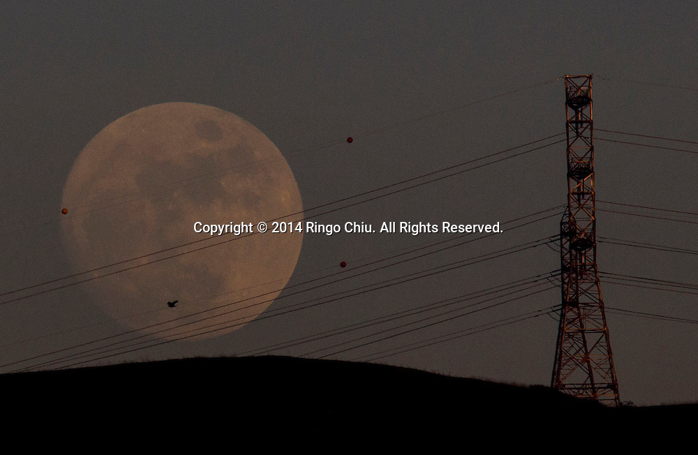 A moon rises behind a hill on Saturday January 3, 2015 in Los Angeles California.