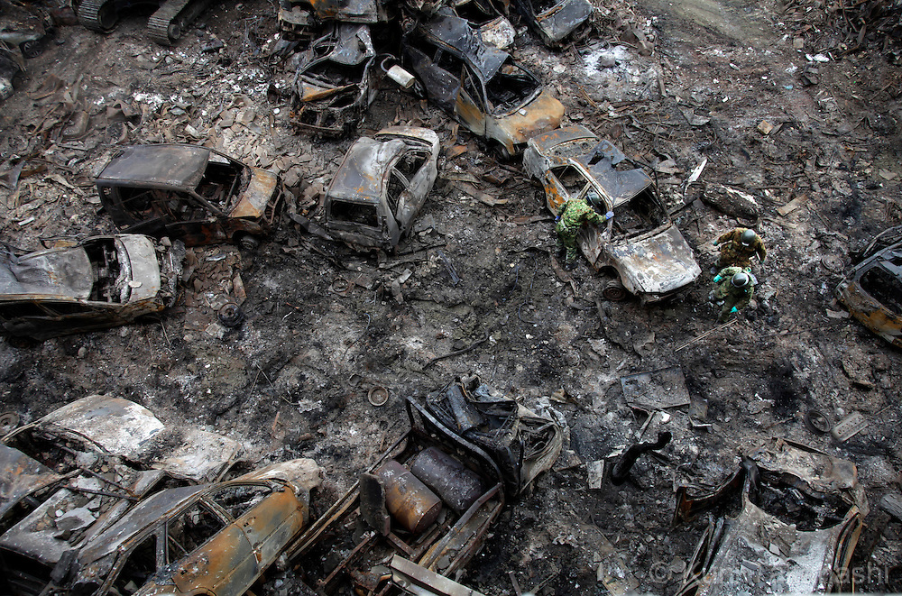 Japanese Self Defense Force solders search bodies of victims below piles of cars which were washed ashore by tsunami and burnt by fire in Ishinomaki, Miyagi, Japan after massive earthquake and tsunami hit northern Japan. More than 20,000 were killed by the disaster on March 11.<br /> Photo by Kuni Takahashi