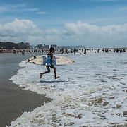 A young boy run happily into the water to surf at Cox's Bazar's beach, Bangladesh