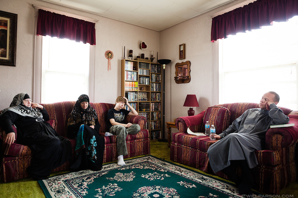 "Khalil sits with Misty, Abdul-Hakim and their friend Ruth, one of the only other Muslims living in Parsons, after Friday morning prayers in the Holmes' living room on March 8, 2013. ""Right now, being Muslim in Parsons, Kansas is really going against the grain,"" Abdul-Hakim said."
