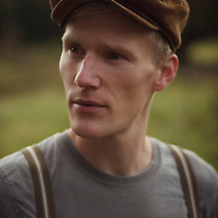 Close portrait of young man wearing a flat cap outdoors looking to the side