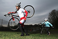 male and female athletes cyclo-cross racers carrying their bicycle up a steep slope.