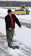 UD Senior Peter Gallant, from Columbus, shovels some snow off the sidewalk, while the heavy equipment clears the parking lot before the women's basketball game at the University of Dayton Arena, January 21, 2007.