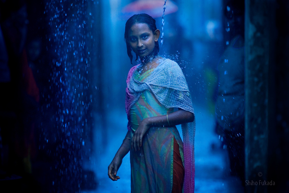 Sex worker Shumita, 12, takes rain shower at brothel, July 17, 2007 in Tangail, Bangladesh. She was born into  brothel. <br /> <br /> Children who are born into brothel have limited opportunity  due to a lack of education, social prejudice, and economic difficulty. Some girls have few options but to follow her mother's footstep as a sex worker, passing the profession on to the next generation.