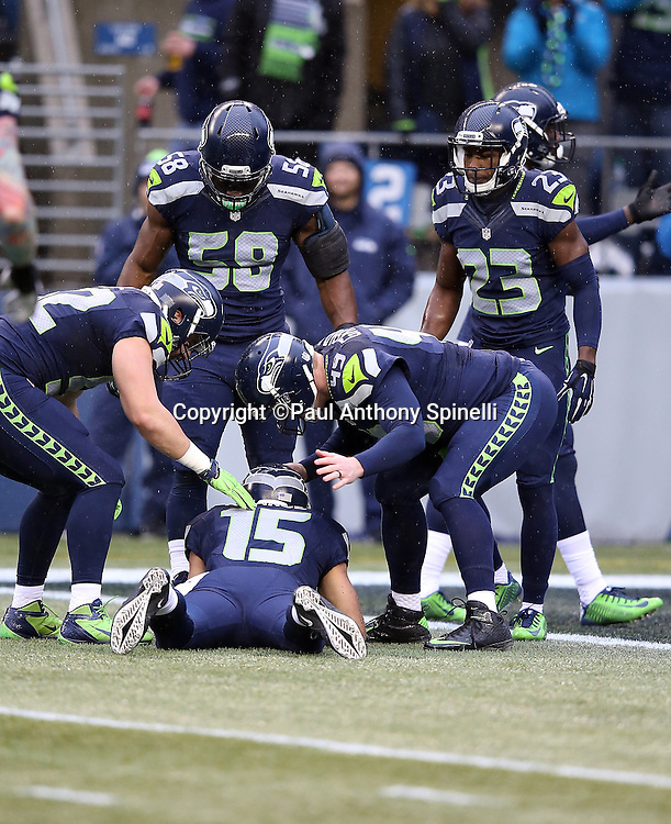 Seattle Seahawks wide receiver Jermaine Kearse (15) gets attention from teammates as he lies on the ground with an injury during the 2015 NFL week 16 regular season football game against the St. Louis Rams on Sunday, Dec. 27, 2015 in Seattle. The Rams won the game 23-17. (©Paul Anthony Spinelli)