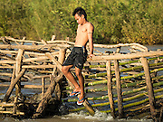 18 JUNE 2016 - DON KHONE, CHAMPASAK, LAOS: A fisherman rests on a fish trap at Khon Pa Soi Waterfalls, on the east side of Don Khon. It's the smaller of the two waterfalls in Don Khon. Fishermen have constructed an elaborate system of rope bridges over the falls they use to get to the fish traps they set. Fishermen in the area are contending with lower yields and smaller fish, threatening their way of life. The Mekong River is one of the most biodiverse and productive rivers on Earth. It is a global hotspot for freshwater fishes: over 1,000 species have been recorded there, second only to the Amazon. The Mekong River is also the most productive inland fishery in the world. The total harvest of fish from the Mekong is approximately 2.5 million metric tons per year. By some estimates the harvest in the Tonle Sap (in Cambodia) had doubled from 1940 to 1995, but the number of people fishing the in the lake has quadrupled, so the harvest per person is cut in half. There is evidence of over fishing in the Mekong - populations of large fish have shrunk and fishermen are bringing in smaller and smaller fish.     PHOTO BY JACK KURTZ