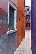 "Purple and orange alley. Burano, known for knitted lacework, fishing, and colorfully painted houses, is a small archipelago of four islands linked by bridges in the Venetian Lagoon, northern Italy, Europe. Burano's traditional house colors are strictly regulated by government. The Romans may have been first to settle Burano. Romantic Venice, the ""City of Canals,"" stretches across 117 small islands in the marshy Venetian Lagoon along the Adriatic Sea in northeast Italy, Europe. Venice and the Venetian Lagoon are honored on UNESCO's World Heritage List."
