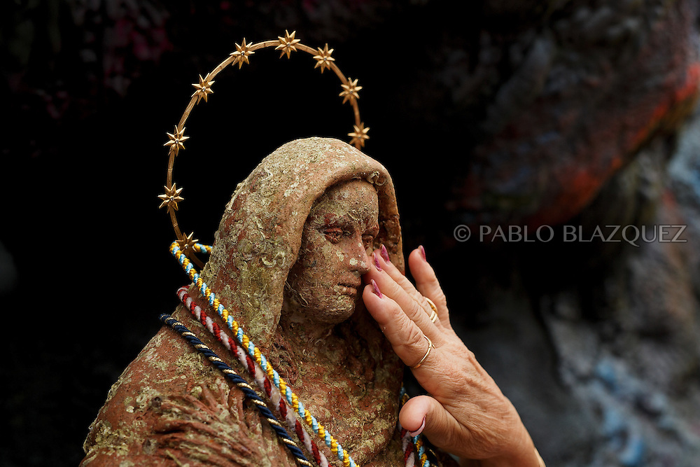 15/08/2016. A worshipper touches the Virgin of Palm image during the yearly Virgin of Palm maritime pilgrimage at El Rinconcillo beach on August 15, 2016 in Algeciras, Spain. The Our Lady of Palm maritime pilgrimage in Algeciras dates back to 1975 and takes place annually when fishermen rescue the submerged virgin from the deep sea. Worshippers amid thousands of visitors await its arrival at the Rinconcillo beach. The devotion for the Virgin of Palm comes from the seventeenth century when a ship coming from Italy docked at Algeciras port to wait out bad weather. According to legend, once the crew of the ship removed a box with an image of the Virgin from its cargo the weather turned and the sea's tides were calmed. (© Pablo Blazquez)