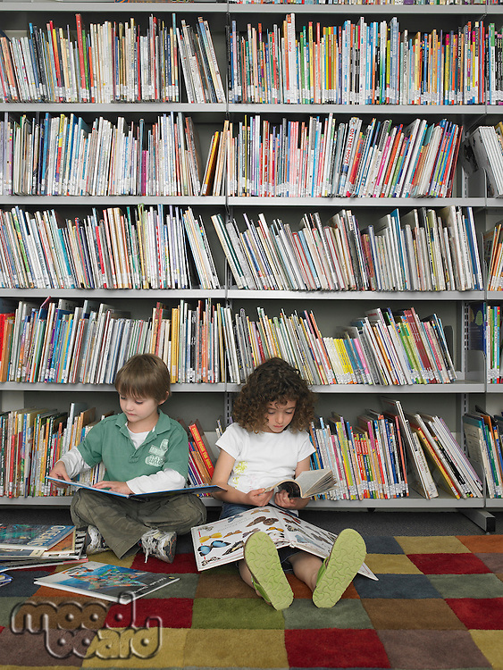 Boy and girl sitting on library floor reading books