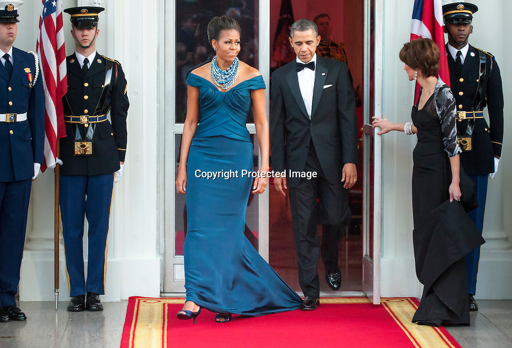 U.S. President Barack Obama steps on first lady Michelle Obama's dress as they walk out to receive Britain's Prime Minister David Cameron and his wife Samantha as they arrive for an official dinner in their honor at the White House in Washington, March 14, 2012.