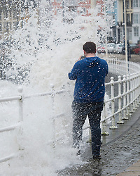 © Licensed to London News Pictures. 27/01/2016. Aberystwyth, UK.  A man gets soaked while taking a photograph as large waves crash against the west coast at Aberystwyth in wales at high tide. The tail end of storm Jonas continues to hit the UK, bringing torrential rain and galesPhoto credit: Keith Morris/LNP