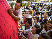 18 NOVEMBER 2015 - BANGKOK, THAILAND:  People sign prayers before the procession at Wat Saket during the parade marking the start of the temple's annual fair. Wat Saket is on a man-made hill in the historic section of Bangkok. The temple has golden spire that is 260 feet high which was the highest point in Bangkok for more than 100 years. The temple construction began in the 1800s in the reign of King Rama III and was completed in the reign of King Rama IV. The annual temple fair is held on the 12th lunar month, for nine days around the November full moon. During the fair a red cloth (reminiscent of a monk's robe) is placed around the Golden Mount while the temple grounds hosts Thai traditional theatre, food stalls and traditional shows.     PHOTO BY JACK KURTZ
