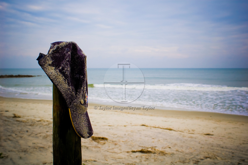 Sandy ballcap on post near ocean surf in Pawleys Island, South Carolina