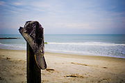 Sandy ballcap on post near ocean surf in Pawleys Island, South Carolina