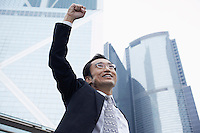 China Hong Kong business man with risen fist low angle view