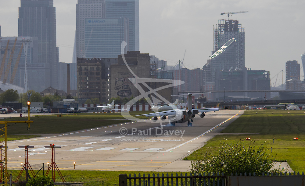 """London City Airport, May 5th 2015. With crosswinds gusting at up to 45 mph, several planes attempting to land at London City Airport have to abort their landings and do a """"go-round"""" whilst others endured rough landings.  PICTURED: A passenger jet edures a rough landing, bouncing from its left to right main landing gear."""