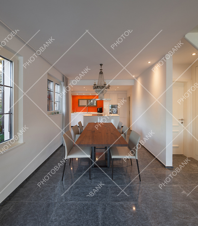 Interior of house, dining room with wooden table, kitchen on background
