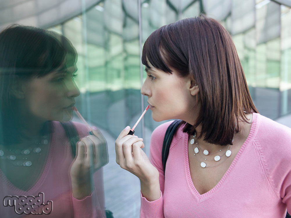 Young woman looking at reflection of self in building window applying lip gloss