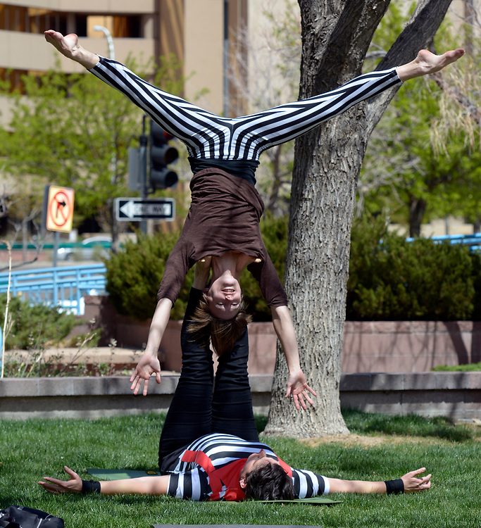 "gbs040217r/ASEC -- Alex Ross-Raymond, top, and Dee Reed,  both of Albuquerque, warm up before performing during the Rally Against Sexual Violence in the Albuquerque Civic Plaza on Sunday, April 2, 2017. They practice ""acroyoga"" as a way to teach sexual violence prevention. (Greg Sorber/Albuquerque Journal)"