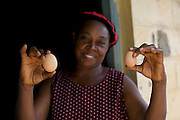 Ijeoma Ewurum proudly showing the improvement in the size of her chickens eggs thanks to the some of the training she received.<br /> <br /> Ijeoma Ewurum used to keep chickens as a hobby but when she retired from her teaching career she set it up as a larger business. <br /> <br /> She attended a business training workshop with Youth for Technology and signed up to receive Business SMS support.<br /> <br /> The main examples of success and impact from the SMS are around innovation and improving product quality; as a result she invested in new feed and vitamins and now has bigger and better eggs and heavier healthier birds. <br /> <br /> What she valued most from the training was learning about capital – she has not heard that word before but now understands the need to reinvest in your business. From the face to face she also valued meeting other women who offered advice.