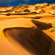 Colorful painterly rendition of orange yellow sand dunes against a stormy dark blue sky