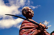 Old man wearing the traditional Tais carrying a sword during the first anniversary of East Timor Independance in Lospalos.. @ Martine Perret. 20 May 2003.