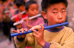 Children take part in music lessons at a school for Tibetan refugees in Dharamsala, India. The Tibetan children's Village runs a chain of fifteen schools, with over ten thousand students, in different parts of India. The main village, known as the Upper TCV, is based on a hill two kilometres from McLeod Ganj. It educates and looks after the upbringing of about three thousand student, most of whom are orphans and new refugees from Tibet. Upper TCV consists of thirty eight homes, four hostels and a baby room to care for months-old infants through to boys and girls of sixteen. It has modern school buildings ranging from nursery to high school, sports grounds, staff quarters, a dispensary, a handicraft centre, etc. These are spread over an area of about forty three acres. (Photo © Jock Fistick)