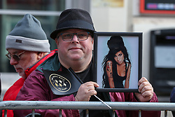 © Licensed to London News Pictures. 04/03/2020. London, UK. AMY WINEHOUSE'S fan holds a photograph of the late British singer who is honoured with a dedicated stone on Camden Music Walk of Fame outside Camden Town tube station. Photo credit: Dinendra Haria/LNP