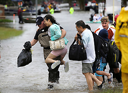 August 29, 2017 - Houston, Texas, U.S. - JULIE HU is carried by a volunteer rescue worker on Westheimer Pkwy, at McMeans Junior HIgh School where First responders as well as volunteers with boats, rescue residents in Kellwood and Cinco Ranch subdivision, on Tuesday. Emergency workers rescued more people in southeast Texas on Tuesday as floodwaters continued to rise. Officials have reported 30 flood-related deaths so far from Hurricane Harvey. (Credit Image: © Bob Owen/San Antonio Express-News via ZUMA Wire)