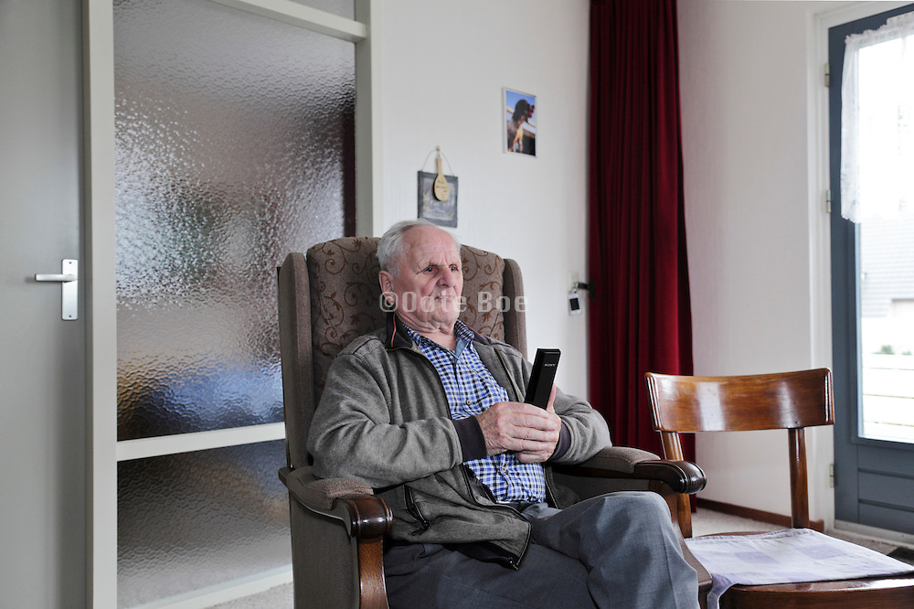 elderly man watching television during daytime