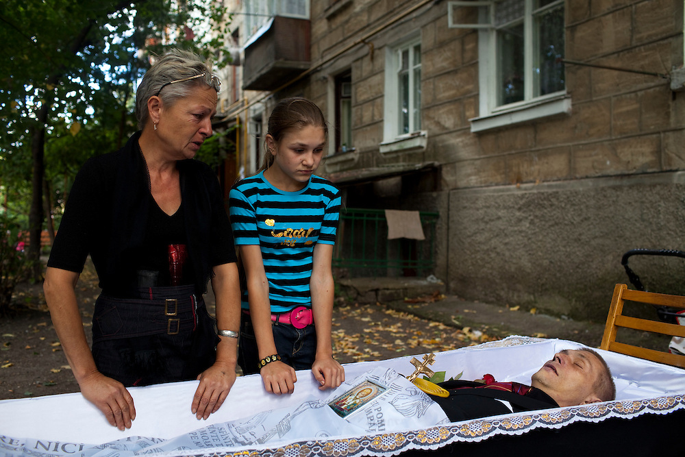 Dumitru Stuplaov was an ex-prisoner who died of MDR-TB.  His mother, Evgenia Stupalov, and daughter, Maria  Stupalov, stand over his body at a wake. ..